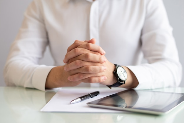 Close-up of male executive sitting at table with clasped hands Free Photo