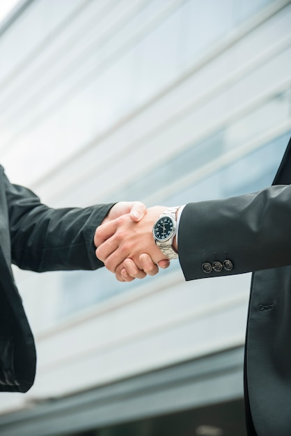Close-up of male and female shaking hands on business deal Free Photo