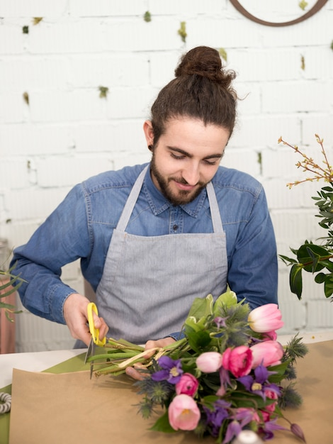 Close-up of a male florist cutting the stem of flower bouquet with scissor Free Photo