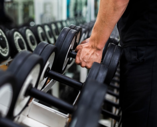 Close-up male at gym choosing weights Free Photo
