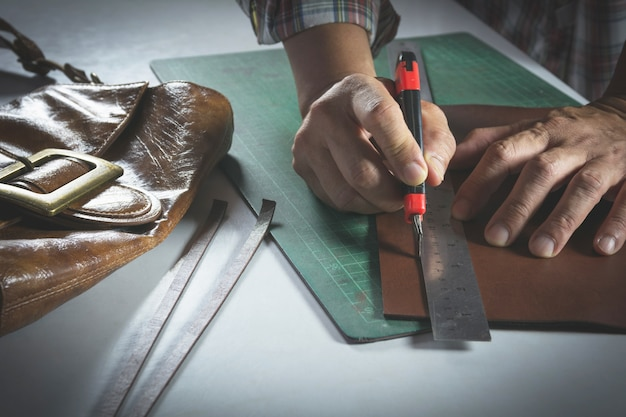 Close-up of male hand cutting with a knife to leather for bag. home made product concept. Premium Photo