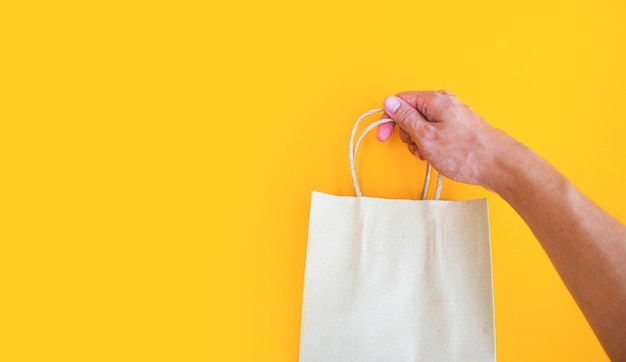 黄色の背景にテイクアウト用の空白の紙袋を穴あけ男性の手を閉じる Premium写真