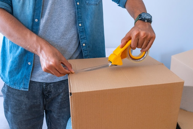 Close up of male hand packing cardboard box Premium Photo
