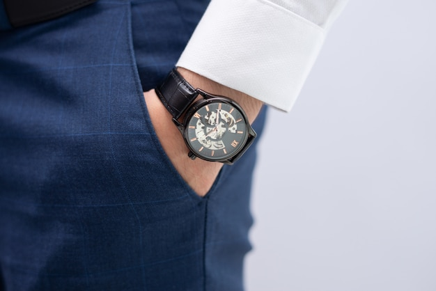 Close-up of male hand in pocket with modern elegant wristwatch Free Photo