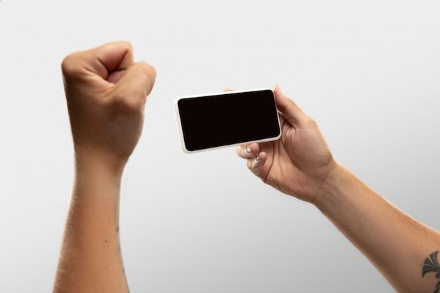 世界中の人気のあるスポーツの試合や選手権をオンラインで見ているときに、空白の画面の電話を持っている男性の手を閉じます。 無料写真