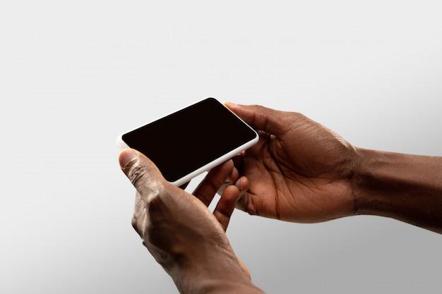 전세계 인기 스포츠 경기 및 선수권 대회 온라인 시청 중 빈 화면으로 전화를 들고 남성 손을 닫습니다. 무료 사진