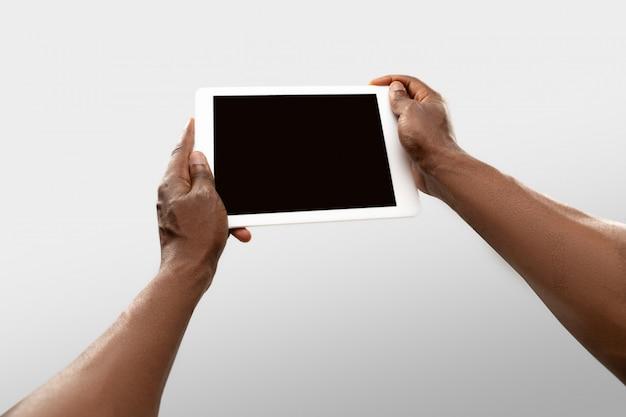 Chiuda sulle mani maschii che tengono la compressa con lo schermo in bianco durante la sorveglianza online delle partite e dei campionati di sport popolari intorno al mondo. Foto Gratuite