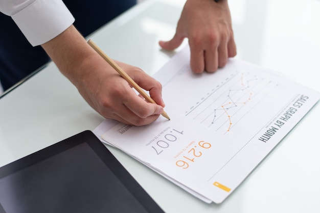 Close-up of male hands writing on sales report in office Free Photo