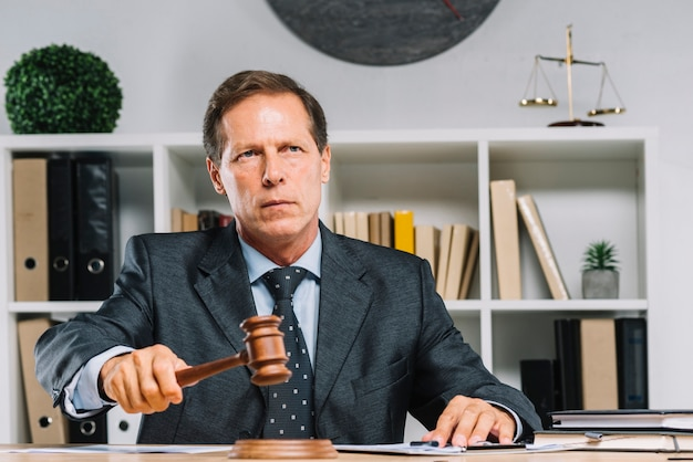 Close up of male judge striking the gavel on wooden block Premium Photo