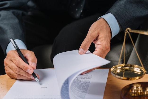 Close-up of male lawyer signing the contract document on the desk Free Photo