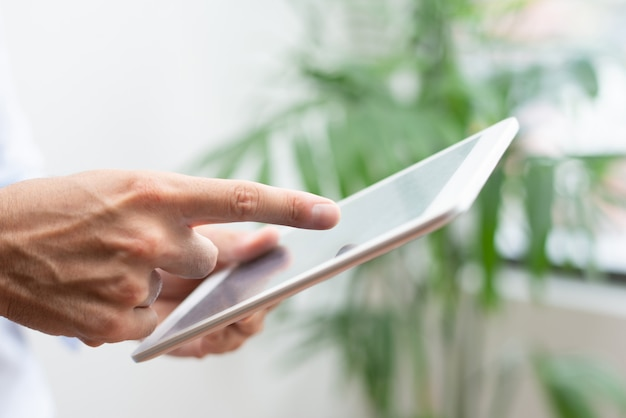 Close-up of male manager showing online data while using tablet Free Photo