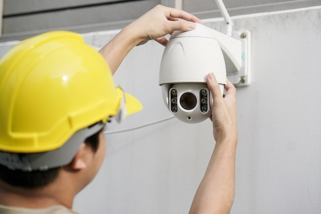 Close up of male technician fixing cctv camera on wall Premium Photo