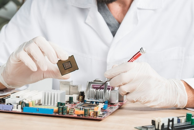 Close-up of a male technician holding computer chip Free Photo
