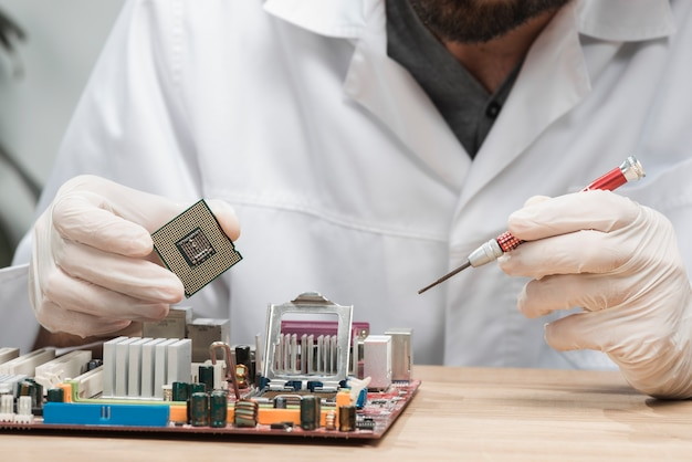 Close-up of a male technician inserting chip in computer motherboard Free Photo