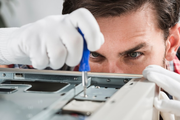 Close-up of a male technician repairing cpu with screwdriver Free Photo