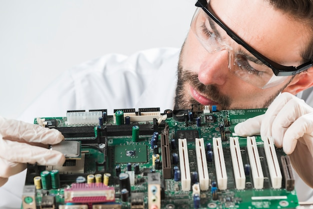 Close-up of a male technician wearing safety glasses inserting chip in computer motherboard Free Photo