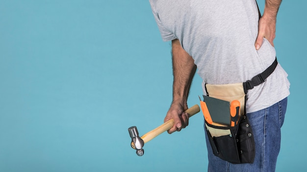 Close-up of a male worker suffering from backpain holding hammer Free Photo