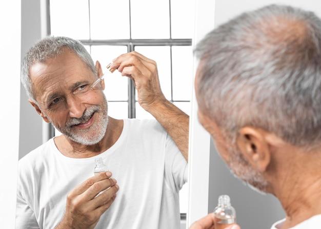 Uomo del primo piano che applica siero del viso Foto Gratuite