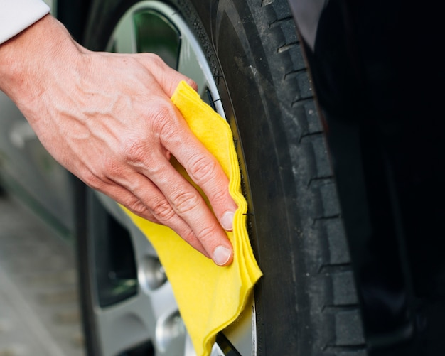Close up of man cleaning car rims Free Photo