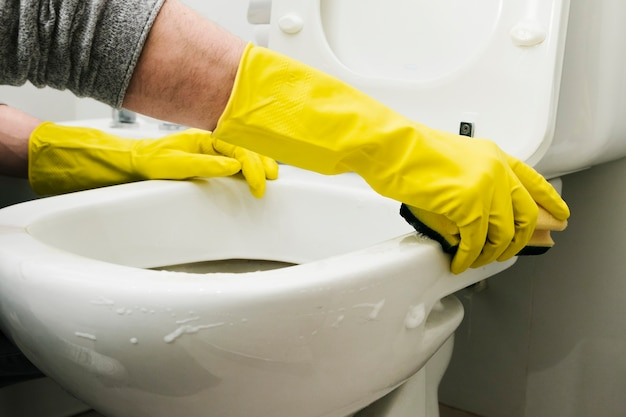 Close up man cleaning toilet with sponge Free Photo