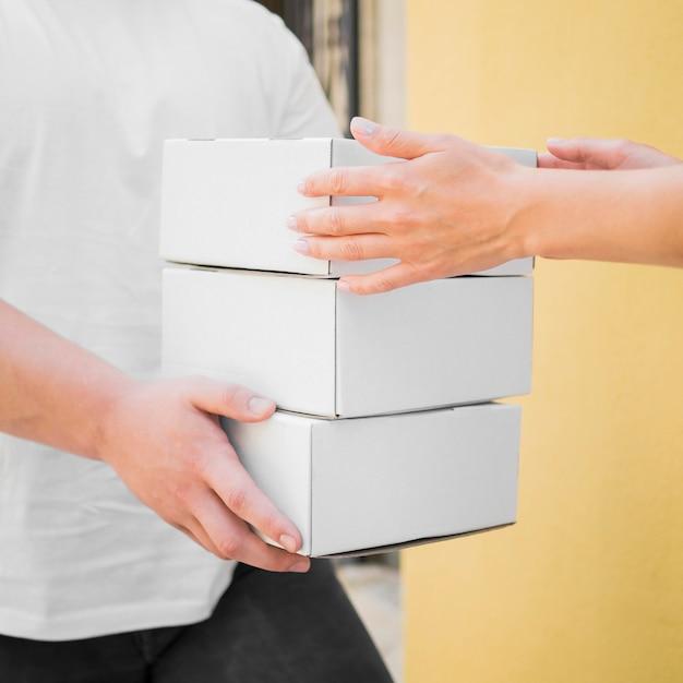 Uomo del primo piano che consegna le scatole Foto Gratuite