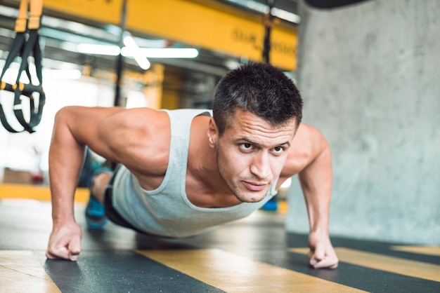 Close-up of a man doing workout in gym Free Photo