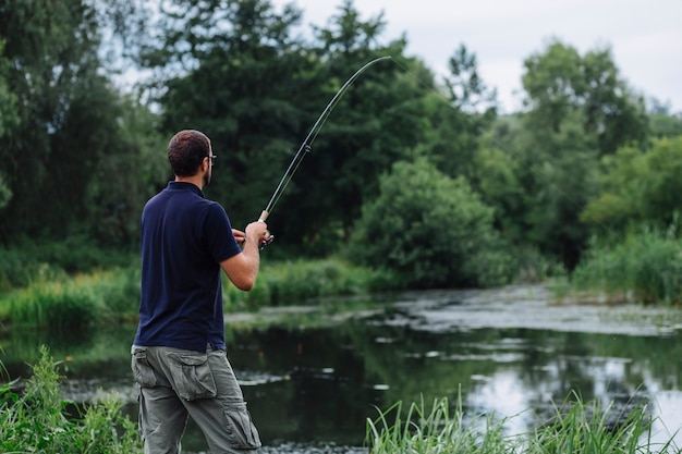 Close-up of man fishing in the lake Free Photo