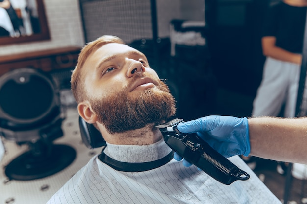 코로나 바이러스 전염병 동안 마스크를 쓰고 이발소에서 머리카락을 자르는 남자를 닫습니다. 무료 사진