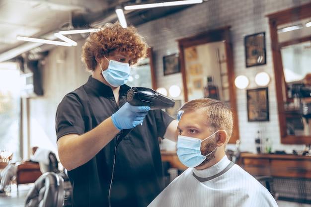 Close up man getting hair cut at the barbershop wearing mask during coronavirus pandemic. Free Photo