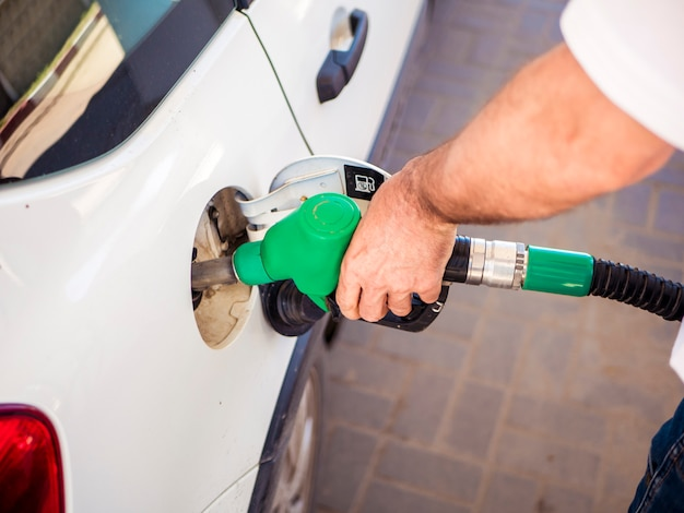 Close up man hand filling the white car with fuel Premium Photo