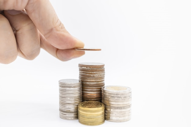 Close up of man hand holding a coin and put it on top of stack of coins on white Premium Photo