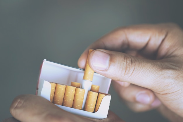 Close up man hand holding peel it off cigarette pack prepare smoking a cigarette. Premium Photo