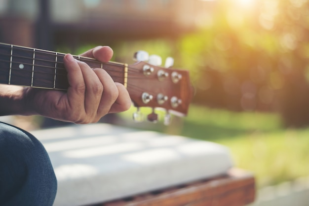 Close up of  man hand playing acoustic guitar. Free Photo