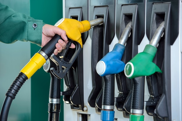 Close-up of a man hand using a fuel nozzle at a gas station. Premium Photo