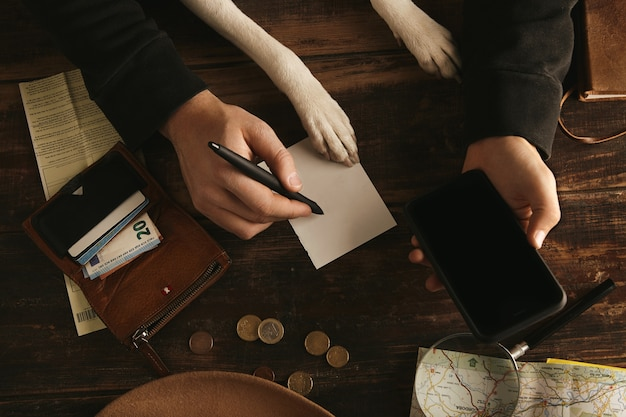 Close up man hands hold smartphone and writes adventure route plan in paper sheet on aged wooden table Free Photo