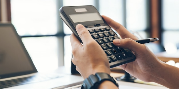 Close up man hands using calculator calculate about cost at home office.tax, accounting, statistics and analytic research concept Premium Photo