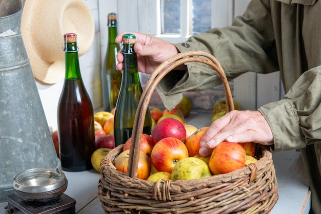 Close up of man hands with a bottle of cider and apples Premium Photo