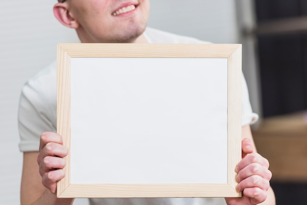 Close-up of a man holding blank white picture frame in front of camera Free Photo