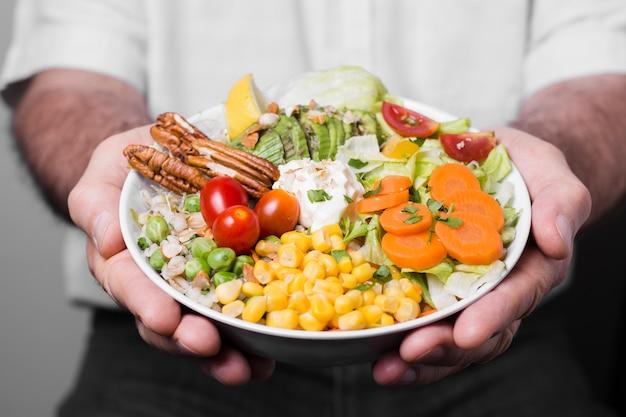 Close-up of man holding bowl of healthy food Free Photo