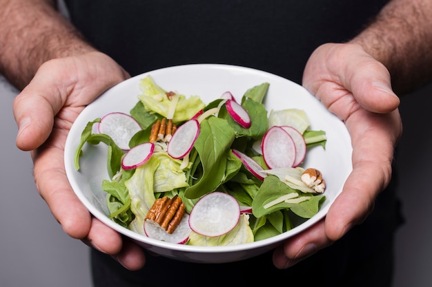 Close-up of man holding bowl of salad in hands Free Photo