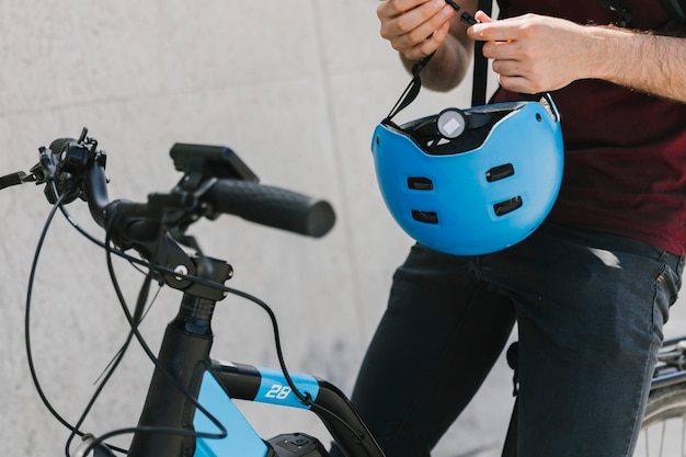 Close up man holding helmet on bicycle Free Photo