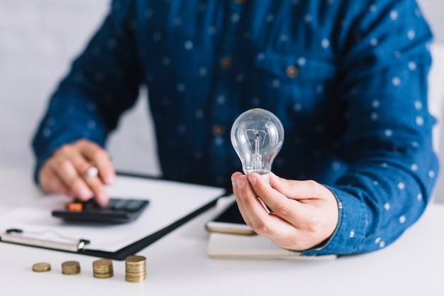 Close-up of man holding lightbulb using calculator at workplace Premium Photo