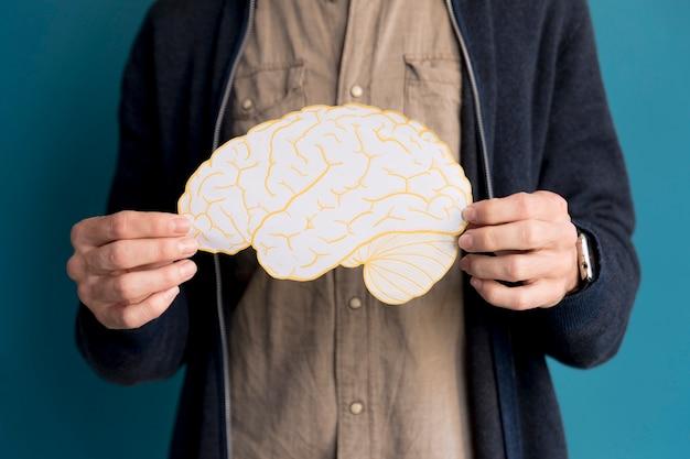 Close-up man holding paper brain Free Photo