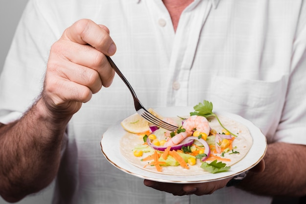 Close-up of man holding plate with healthy food Free Photo