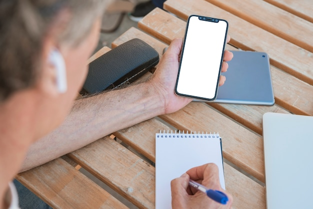 Close-up of a man holding smartphone writing on spiral notepad with pen Free Photo