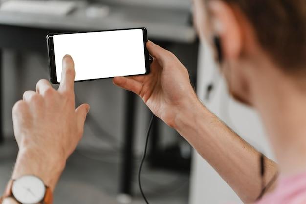 Крупным планом мужчина держит смартфон Бесплатные Фотографии