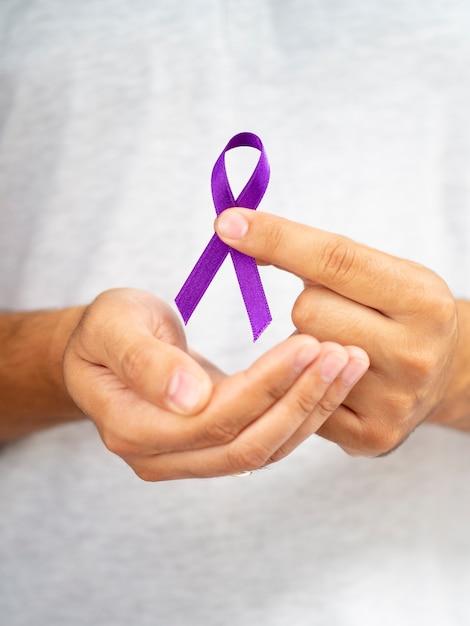 Close-up man holding up purple ribbon Free Photo