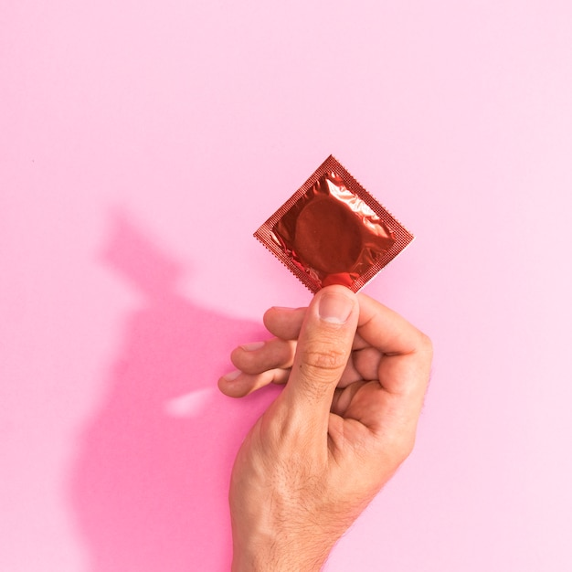 Close-up man holding up a red condom Free Photo