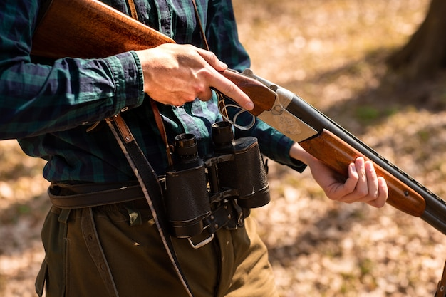Close-up of a man holding weapons in the woods Premium Photo