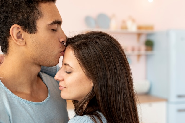 Close-up man kissing woman on the forehead | Free Photo